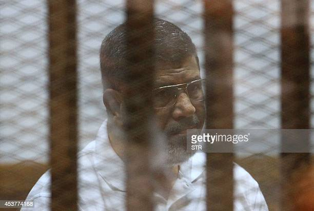 Egypt's deposed Islamist president Mohamed Morsi, charged along with 130 others of plotting attacks and escaping from prison in 2011, sits inside the...