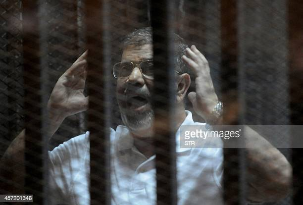 Egypt's deposed Islamist president Mohamed Morsi gestures inside the defendants cage during his trial at the police academy in Cairo on October 14,...