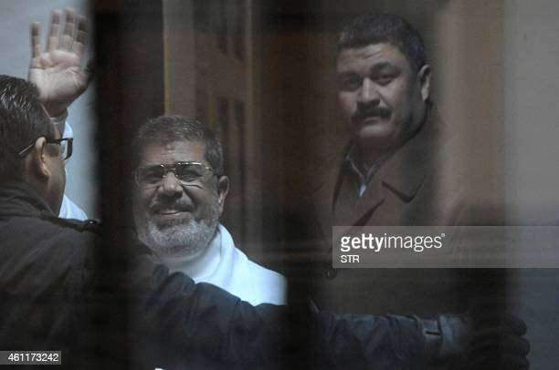 Egypt's deposed Islamist president Mohamed Morsi waves from inside the defendants cage during his trial at the police academy in Cairo on January 8,...
