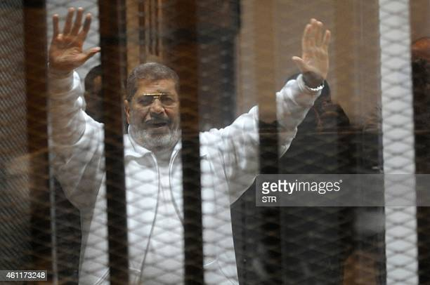 Egypt's deposed Islamist president Mohamed Morsi waves from inside the defendants cage during his trial at the police academy in Cairo on January 8...