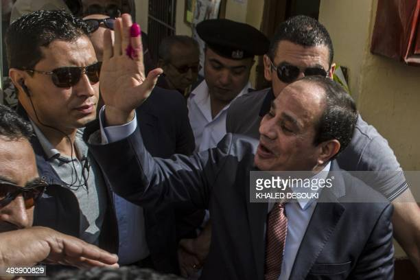Egypt's exarmy chief and leading presidential candidate Abdel Fattah alSisi salutes the crowd after casting his vote at a polling station in the...