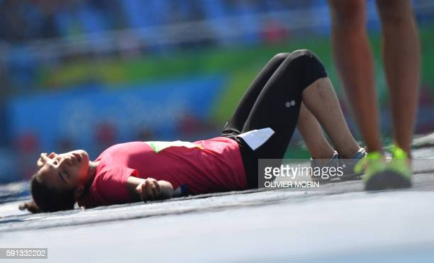 Egypt's Fatma Nagib El Sharnouby lies on the track after she fainted following the Women's 800m Round 1 during the athletics event at the Rio 2016...