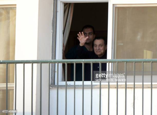 Egypt's former president Hosni Mubarak waves from his room at the Maadi military hospital in Cairo on May 4 2015 as his supporters gather outside the...