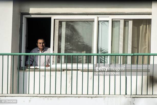 Egypt's former president Hosni Mubarak waves to people from his room at the Maadi military hospital in Cairo on October 6 2016 as his supporters...