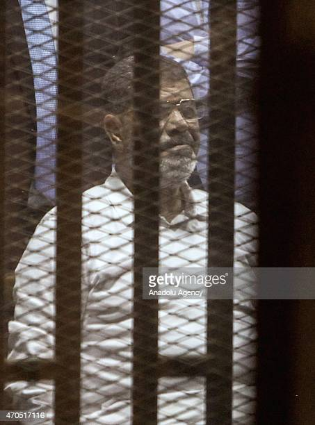 Egypt's former president Mohammed Morsi looks from behind dock bars during trial session in Cairo Egypt on 21 April 2015 An Egyptian court sentenced...