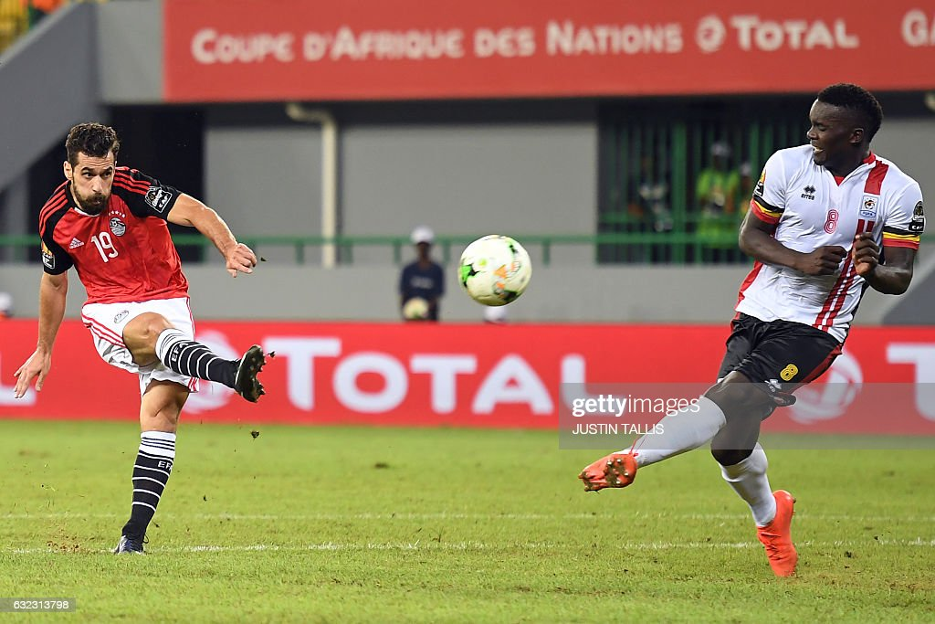 TOPSHOT - Egypt's forward Abdallah Said (L) kicks the ball past Uganda's midfielder Khalid Aucho during the 2017 Africa Cup of Nations group D football match between Egypt and Uganda in Port-Gentil on January 21, 2017. / AFP / Justin TALLIS