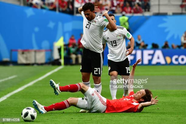 Egypt's forward Mahmoud 'Trezeguet' Hassan and Egypt's midfielder Abdallah Said vies with Russia's defender Mario Fernandes during the Russia 2018...