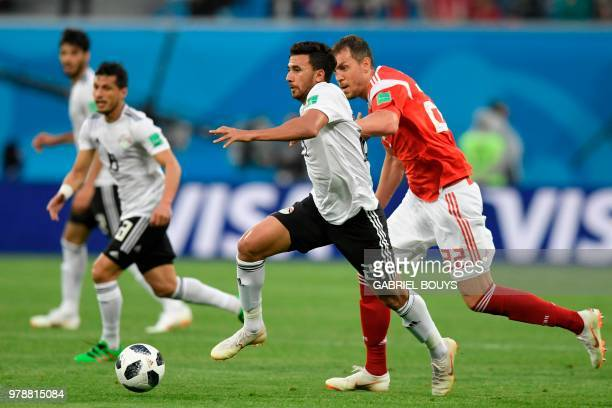 Egypt's forward Mahmoud 'Trezeguet' Hassan and Russia's forward Artem Dzyuba vie during the Russia 2018 World Cup Group A football match between...