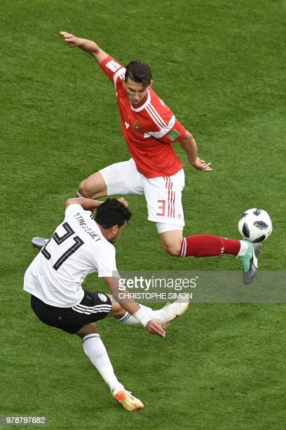 Egypt's forward Mahmoud 'Trezeguet' Hassan attempts a shot as he is marked by Russia's defender Ilja Kutepov during the Russia 2018 World Cup Group A...