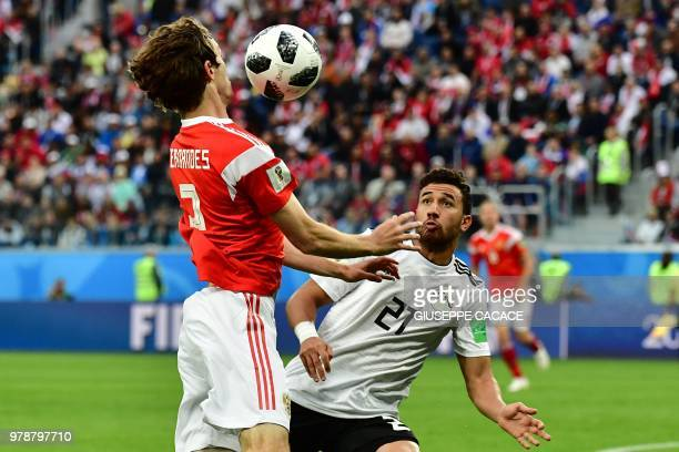Egypt's forward Mahmoud 'Trezeguet' Hassan fights for the ball with Russia's defender Mario Fernandes during the Russia 2018 World Cup Group A...