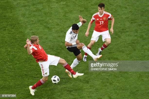 Egypt's forward Mahmoud 'Trezeguet' Hassan vies for the ball with Russia's midfielder Yuri Gazinskiy and Russia's midfielder Aleksandr Golovin during...