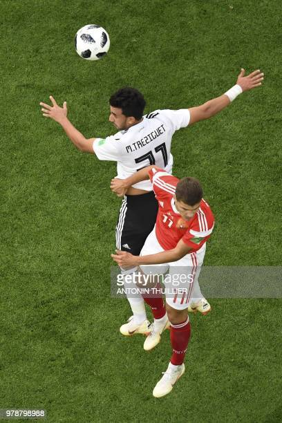 Egypt's forward Mahmoud 'Trezeguet' Hassan vies for the header with Russia's midfielder Roman Zobnin during the Russia 2018 World Cup Group A...