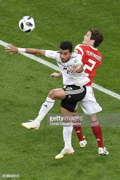 Egypt's forward Mahmoud 'Trezeguet' Hassan vies for the header with Russia's defender Mario Fernandes during the Russia 2018 World Cup Group A...