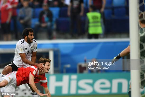 Egypt's forward Marwan Mohsen tries to score against Russia's defender Mario Fernandes and Russia's goalkeeper Igor Akinfeev during the Russia 2018...