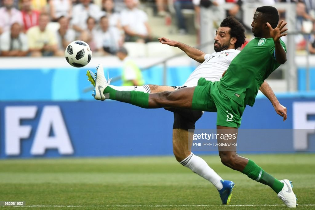 TOPSHOT - Egypt's forward Mohamed Salah (L) and Saudi Arabia's defender Osama Hawsawi fight for the ball during the Russia 2018 World Cup Group A football match between Saudi Arabia and Egypt at the Volgograd Arena in Volgograd on June 25, 2018. (Photo by Philippe DESMAZES / AFP) / RESTRICTED