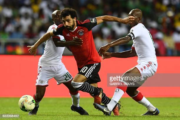 TOPSHOT Egypt's forward Mohamed Salah challenges Burkina Faso's midfielder Charles Kabore and Burkina Faso's defender Yacouba Coulibaly during the...