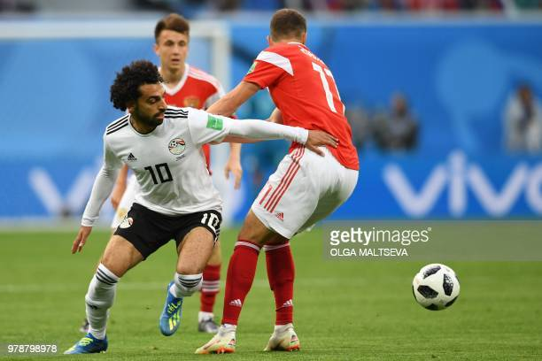 Egypt's forward Mohamed Salah fights for the ball with Russia's midfielder Roman Zobnin during the Russia 2018 World Cup Group A football match...