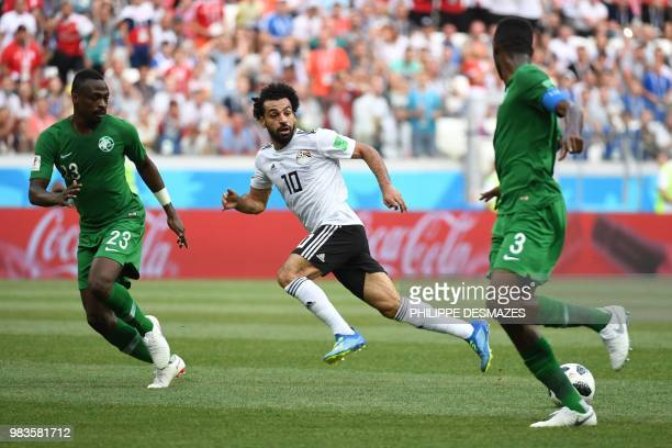 Egypt's forward Mohamed Salah fights for the ball with Saudi Arabia's defenders Motaz Hawsawi and Osama Hawsawi during the Russia 2018 World Cup...