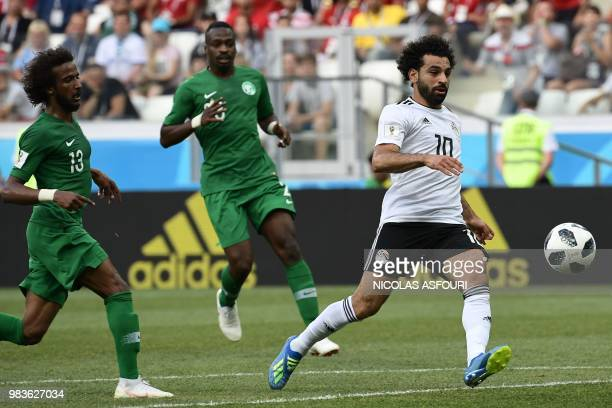 Egypt's forward Mohamed Salah fights for the ball with Saudi Arabia's defenders Yasser AlShahrani and defender Motaz Hawsawi during the Russia 2018...