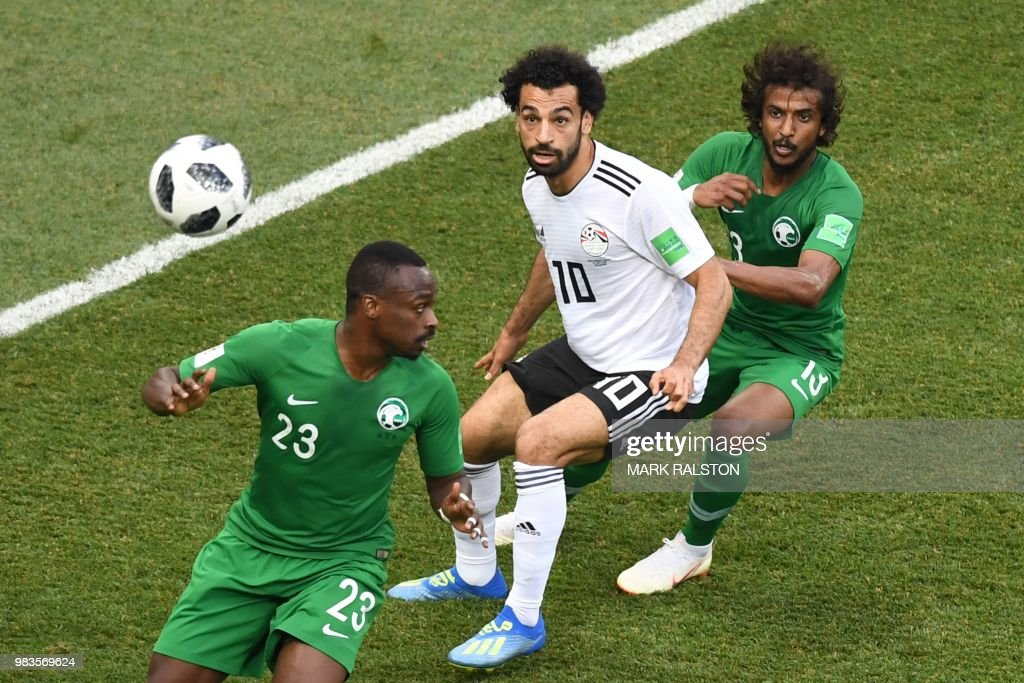 Egypt's forward Mohamed Salah (C) is marked by Saudi Arabia's defender Yasser Al-Shahrani (R) as the cross comes in during the Russia 2018 World Cup Group A football match between Saudi Arabia and Egypt at the Volgograd Arena in Volgograd on June 25, 2018. (Photo by Mark RALSTON / AFP) / RESTRICTED