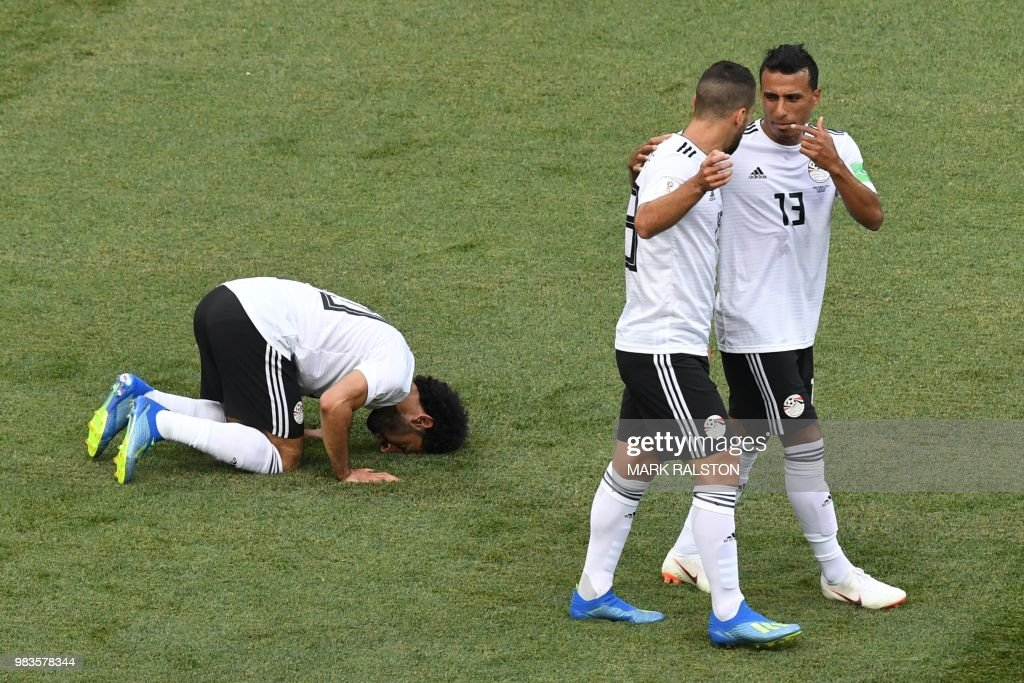 TOPSHOT - Egypt's forward Mohamed Salah (L) kneels to celebrate his opening goal during the Russia 2018 World Cup Group A football match between Saudi Arabia and Egypt at the Volgograd Arena in Volgograd on June 25, 2018. (Photo by Mark RALSTON / AFP) / RESTRICTED