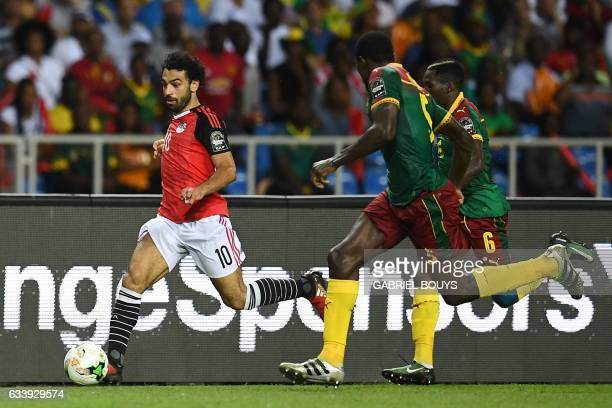 Egypt's forward Mohamed Salah runs with the ball chased by Cameroon's defender Michael NgadeuNgadjui and Cameroon's defender Ambroise Oyongo during...