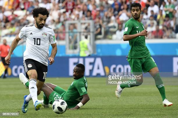 Egypt's forward Mohamed Salah runs with the ball past Saudi Arabia's defender Motaz Hawsawi and midfielder Hussain Al Moqahwi during the Russia 2018...