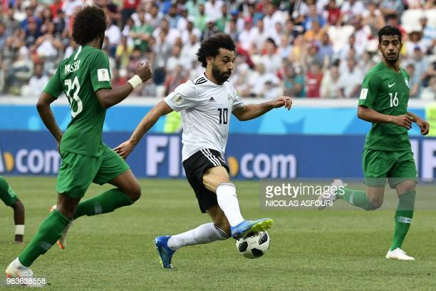 Egypt's forward Mohamed Salah runs with the ball past Saudi Arabia's defender Yasser AlShahrani and midfielder Hussain Al Moqahwi during the Russia...