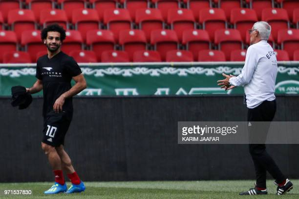 Egypt's forward Mohamed Salah speaks with Egypt's national team head coach Hector Cuper during a training session of Egypt's national football team...