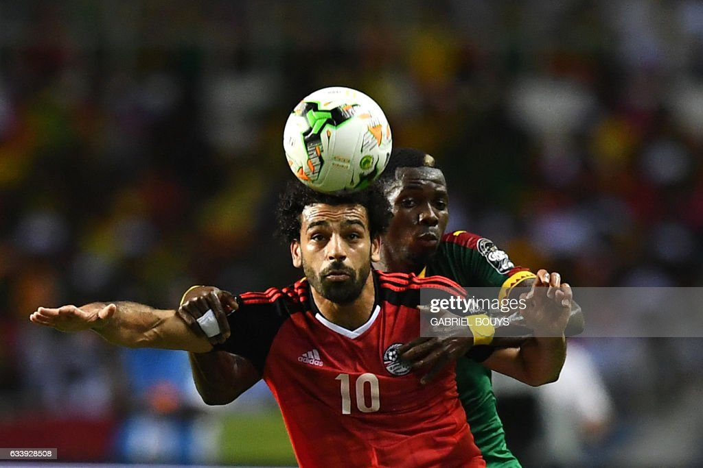 Egypt's forward Mohamed Salah (front) vies for the ball against Cameroon's defender Ambroise Oyongo during the 2017 Africa Cup of Nations final football match between Egypt and Cameroon at the Stade de l'Amitie Sino-Gabonaise in Libreville on February 5, 2017. /