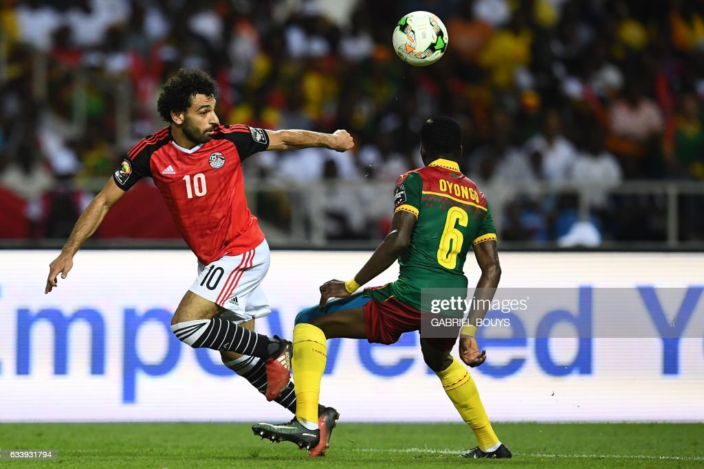 Egypt's forward Mohamed Salah (L) vies for the ball against Cameroon's defender Ambroise Oyongo during the 2017 Africa Cup of Nations final football match between Egypt and Cameroon at the Stade de l'Amitie Sino-Gabonaise in Libreville on February 5, 2017. / AFP / GABRIEL