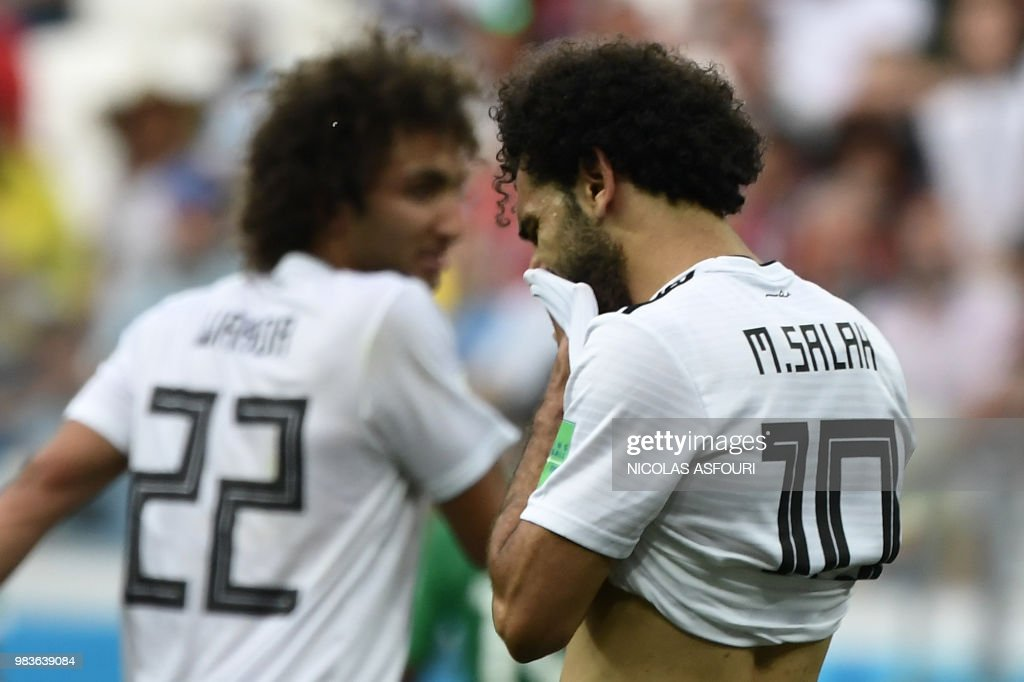TOPSHOT - Egypt's forward Mohamed Salah (R) wipes his face during the Russia 2018 World Cup Group A football match between Saudi Arabia and Egypt at the Volgograd Arena in Volgograd on June 25, 2018. (Photo by NICOLAS ASFOURI / AFP) / RESTRICTED