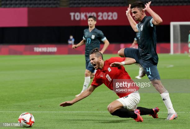 Egypt's forward Ramadan Sobhi falls on the pitch beside Argentina's defender Hernan De La Fuente during the Tokyo 2020 Olympic Games men's group C...