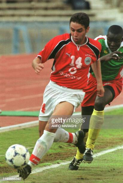 Egypt's Hazam Imam chases the ball as Burkina Faso's Traore Ousmano trys to stop him during their African Friendly soccer match 11 January 2002 in...