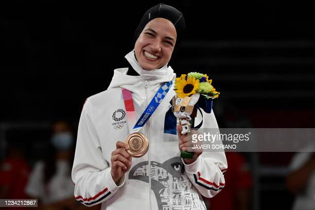Egypt's Hedaya Wahba poses on the podium after the taekwondo women's -67kg gold medal bouts during the Tokyo 2020 Olympic Games at the Makuhari Messe...