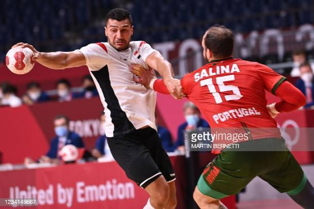 Egypt's left back Yehia Elderaa is challenged during the men's preliminary round group B handball match between Portugal and Egypt during the Tokyo...