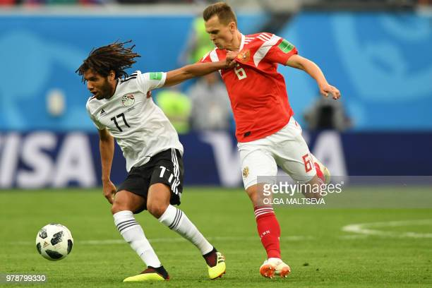 Egypt's midfielder Mahmoud 'Kahraba' AbdelMoneim fights for the ball with Russia's midfielder Denis Cheryshev during the Russia 2018 World Cup Group...