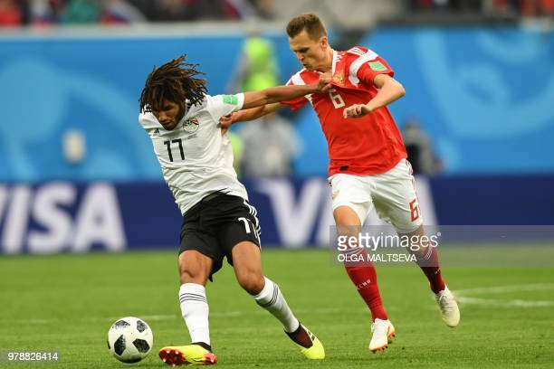 Egypt's midfielder Mohamed Elneny vies with Russia's midfielder Denis Cheryshev during the Russia 2018 World Cup Group A football match between...