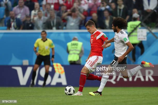 Egypt's Mohamed Elneny and Russia's Roman Zobnin vie for the ball during the FIFAWorld Cup 2018 Group A soccer match between Egypt and Russia at the...