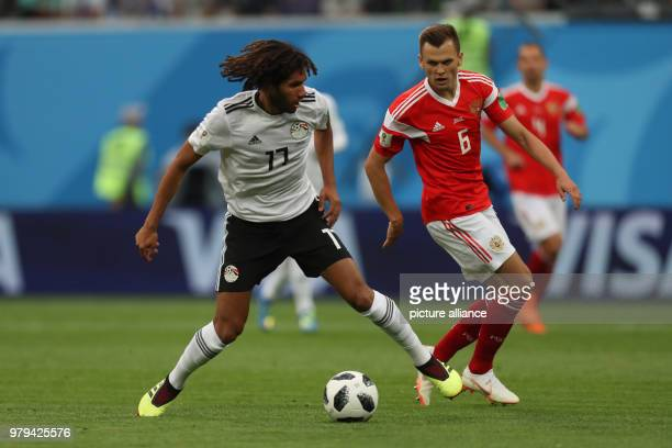 Egypt's Mohamed Elneny vies for the ball with Russia's Denis Cheryshev during the FIFAWorld Cup 2018 Group A soccer match between Egypt and Russia...