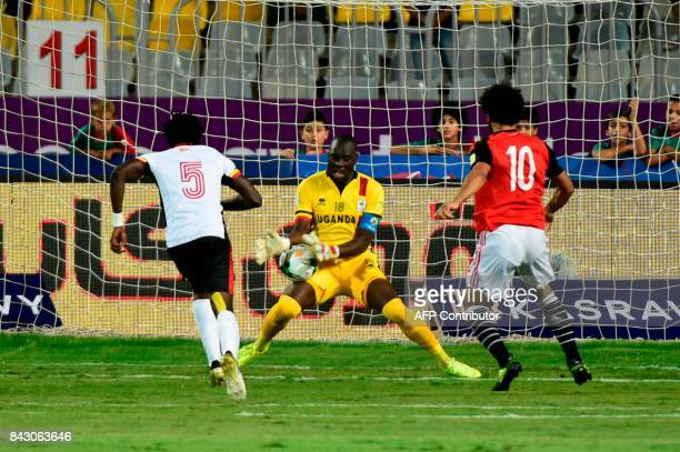Egypts Mohamed Salah takes a shot on goal as Ugandas goalkeeper Denis Onyango defends during the FIFA World Cup 2018 qualification football match...