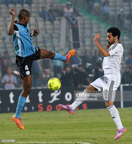 Egypts Mohamed Salah vies for the ball with Botswanas Mosha Gaolaolwe during the 2015 Africa Cup of Nations qualifying football match between Egypt...