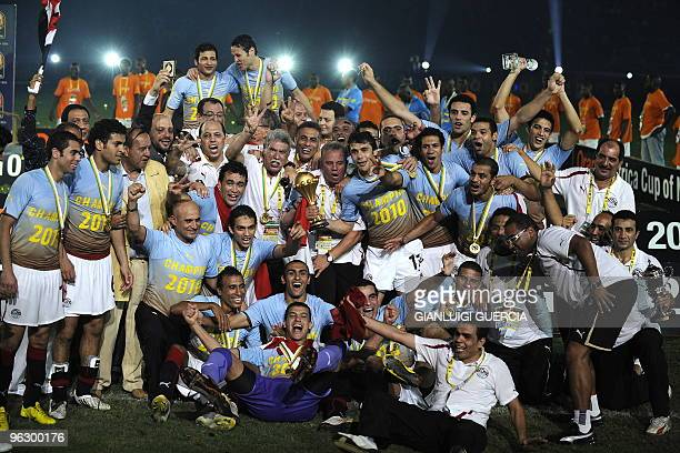 Egypt's national football team players react as they hold up the African Cup of Nations trophy after winning their final match against Ghana of the...