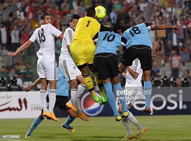 Egypts national team goalkeeper Ahmed ElShenawy fights for the ball against Botswanas players Kenano Kgetholetsile and Mogogi Gabonamong during their...