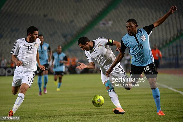 Egypts national team players Ahmed Fathy and Mohamed ElNenny fight for the ball against Botswanas Mogogi Gabonamong during their Africa Cup of...