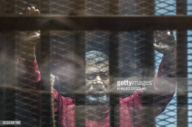 Egypt's ousted Islamist president Mohamed Morsi, wearing a red uniform, gestures from behind the bars during his trial in Cairo at the police academy...