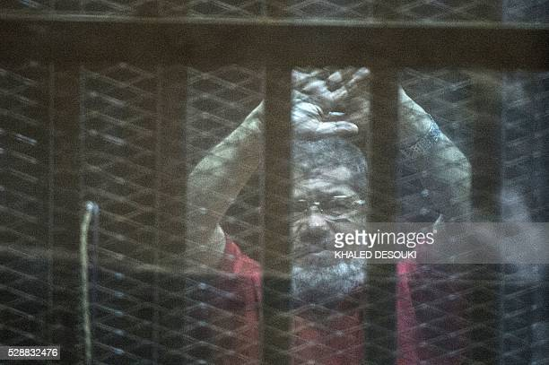 Egypt's ousted Islamist president Mohamed Morsi, wearing a red uniform, gestures from behind the defendant's bars during his trial at the police...