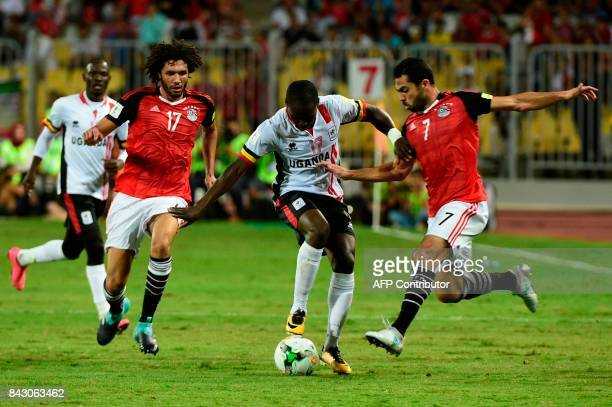 Egypts players Ahmed Fathy and Mohamed elNenny challenge Ugandas Farouk Miya for the ball during the FIFA World Cup 2018 qualification football match...