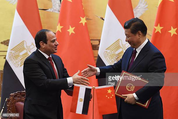 Egypt's President Abdel Fattah alSisi greets Chinese President Xi Jinping during a signing ceremony at the Great Hall of the People on December 23...