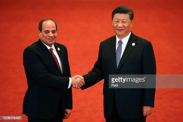 Egypt's President Abdel Fattah alSisi left shakes hands with Chinese President Xi Jinping as they pose for photographers during the Forum on...